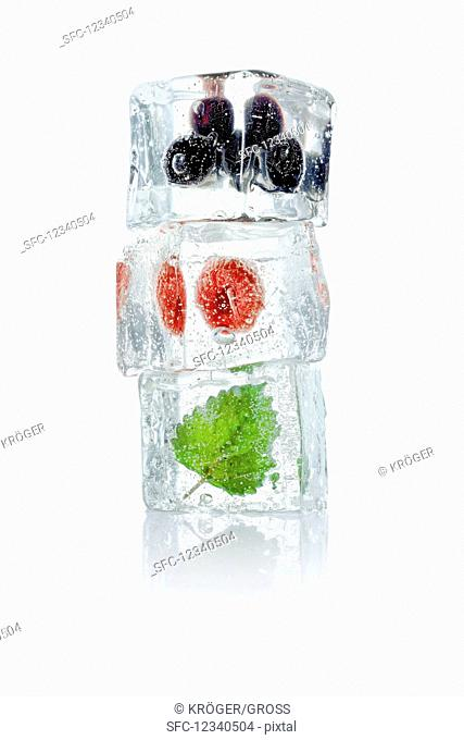 Ice cubes with blueberries, raspberries and melissa