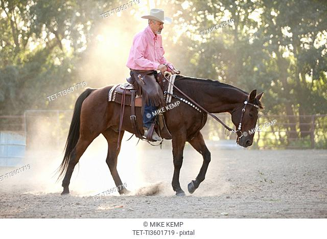 Senior man horseback riding in ranch