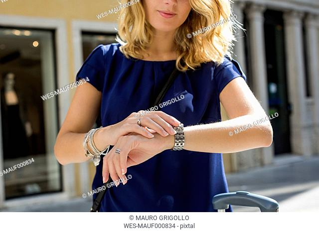 Blond woman checking the time, partial view