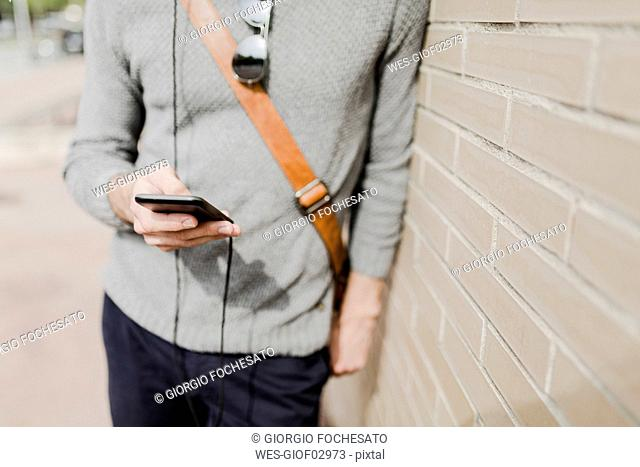 Young man with leaning against wall using cell phone, partial view