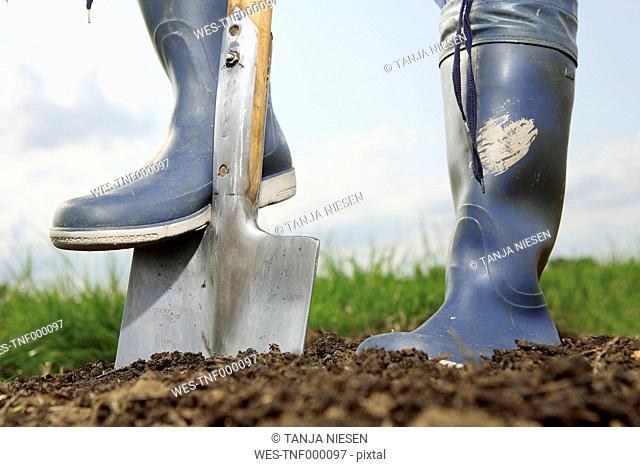 Germany, Bavaria, Human legs with spade on field
