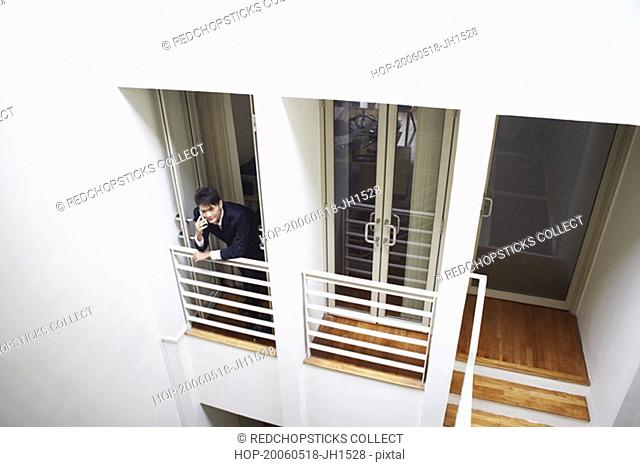 High angle view of a businessman standing at the doorway in an office and talking on a mobile phone