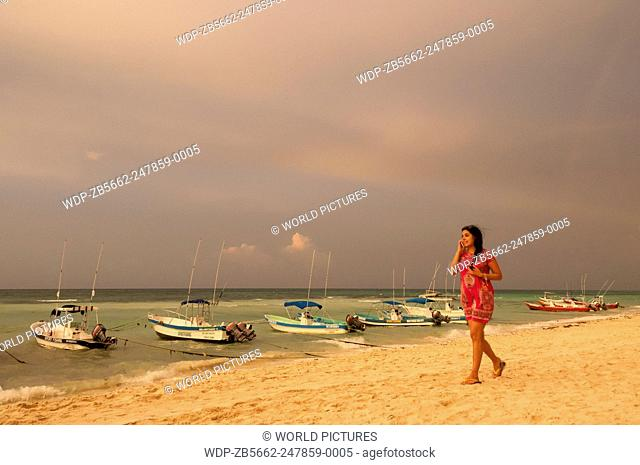 Woman talking on cell phone and walking on beach at Playa del Carmen, Riviera Maya, Mexico