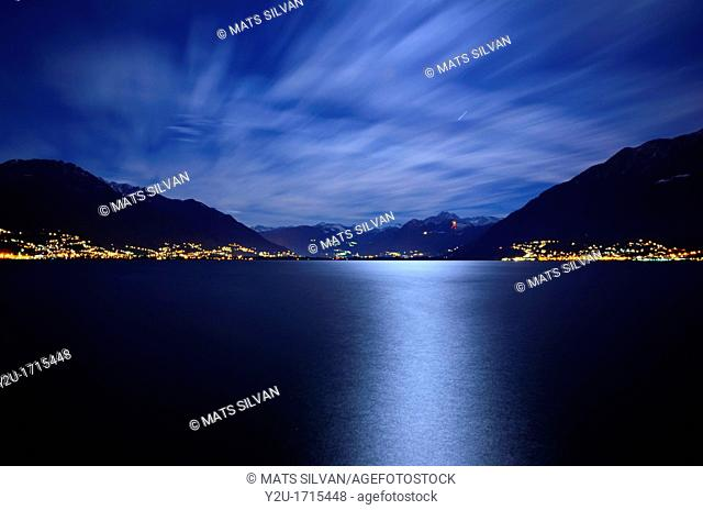 Reflected moon light over an alpine lake maggiore with snow-capped mountains and clouds in ticino switzerland