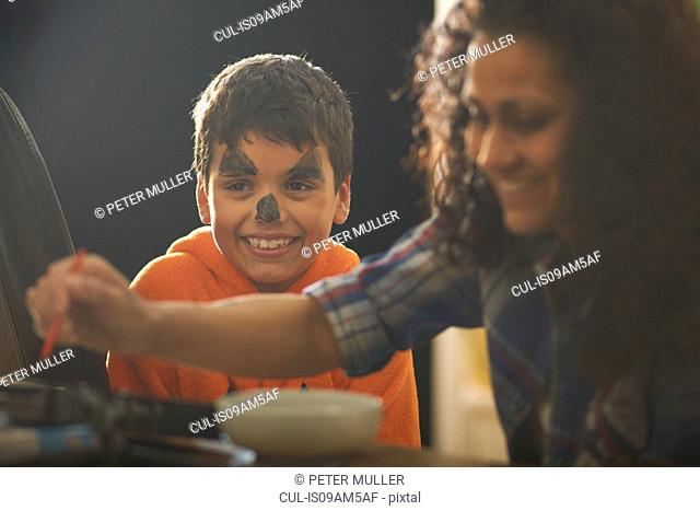 Mother painting sons pumpkin face for halloween