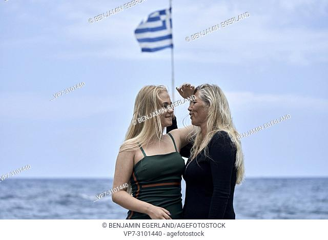 mother (43 years) with teenage girl (13 years) next to greek flag at seaside. Danish ethnicity. In Chersonissos, Crete, Greece