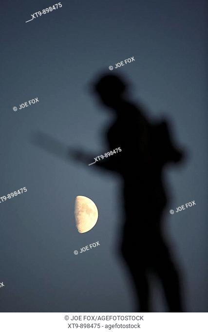 partial moon rising over war memorial statue of world war british soldier in portstewart county londonderry northern ireland uk