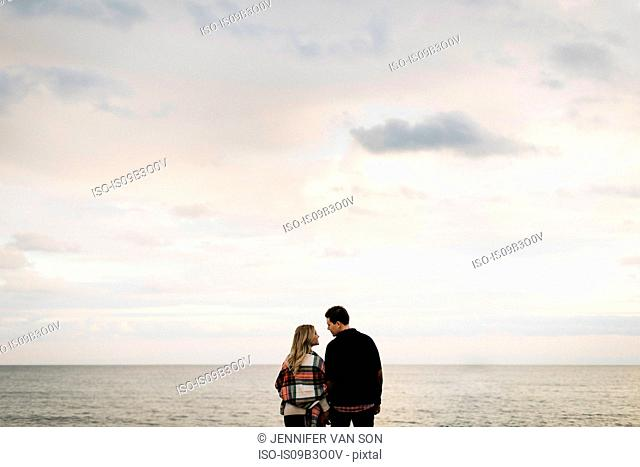 Young couple outdoors, beside sea, rear view