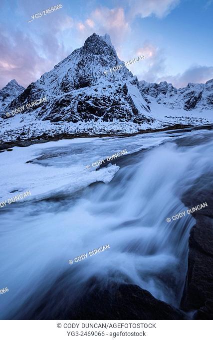 Stortinden mountain peak rises over waterfall in winter, Flakstadøy, Lofoten Islands, Norway