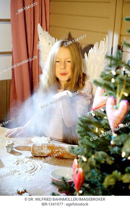 Little girl dressed as an angel baking Christmas cookies