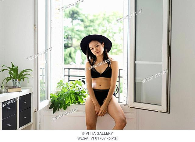 Portrait of attractive young woman wearing hat and lingerie sitting at the window