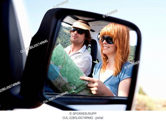 Couple with map in car mirror