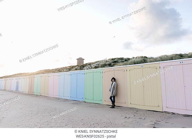 Woman leaning against beach hut