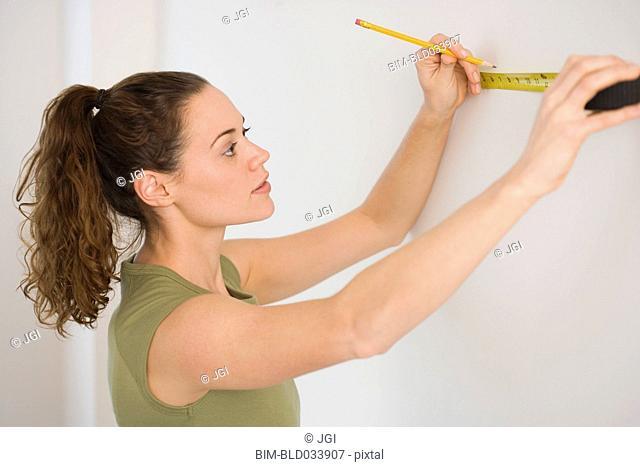 Hispanic woman using tape measure on wall