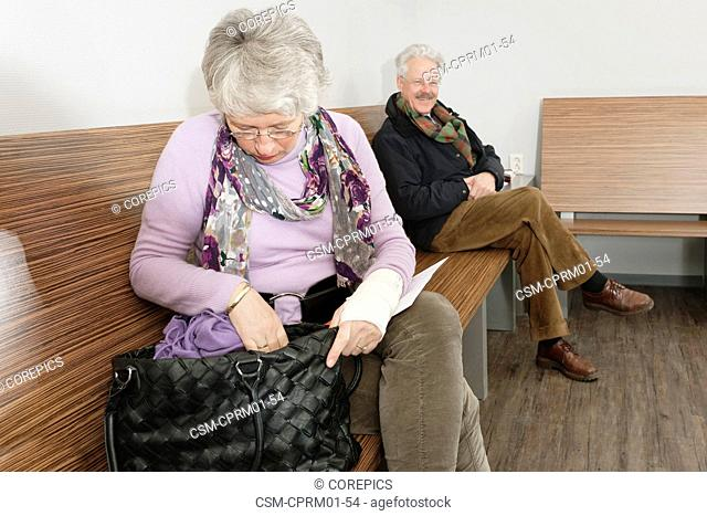 Elderly woman looking through her belongings in the waiting room of a hospital clinic