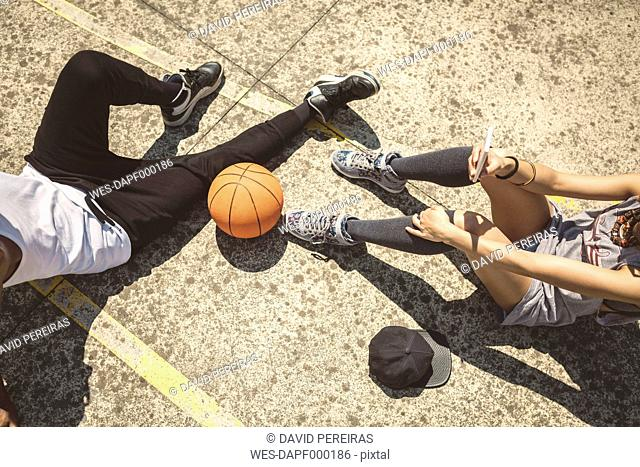 Young couple sitting on ground with basketball and smart phone