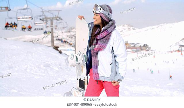 Young woman surveying the snow mountain slopes after alighting from the ski lift at a mountain ski resort as she holds her snowboard