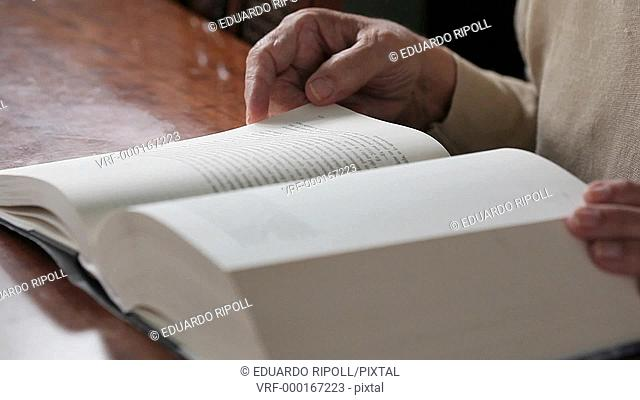 Closeup of a hand turning the pages of a book