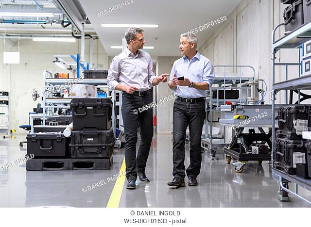 Two businessmen walking in factory hall