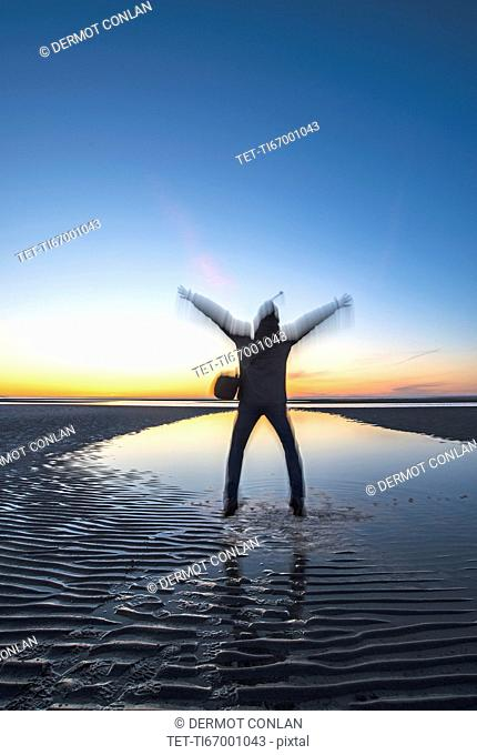 USA, Massachusetts, Cape Cod, Orleans, Man jumping on beach at sunset