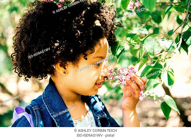 Portrait of girl smelling flowers, side view
