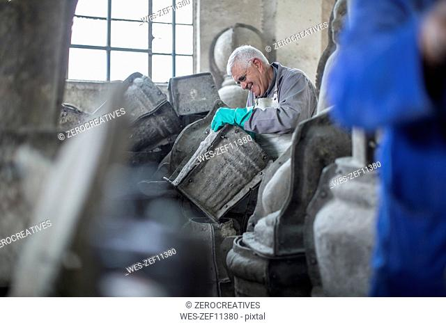 Smiling man working in industrial pot factory