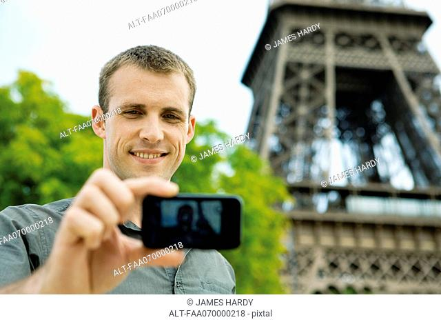 Man photographing himself in front of Eiffel Tower, Paris, France