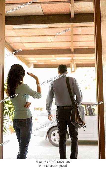 India, Woman waving goodbye at front door and man going to car