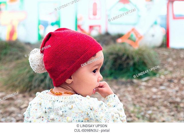 Toddler in red beanie with pom pom