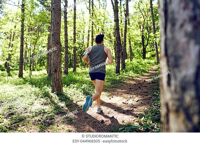 A young male runner runs in the forest in the summer