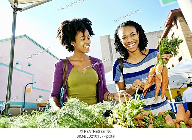 Women shopping together at vegetable stand