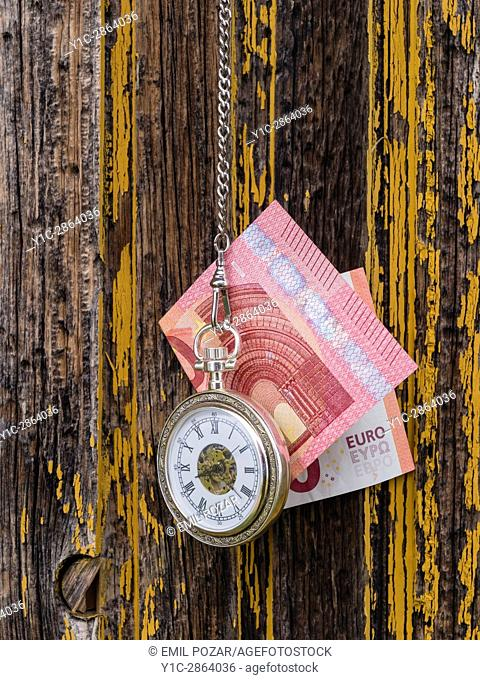 Time is money euro and vintage pocket watch clock before derelict rotten wooden wall