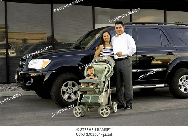 Young Hispanic family standing next to sports utility vehicle
