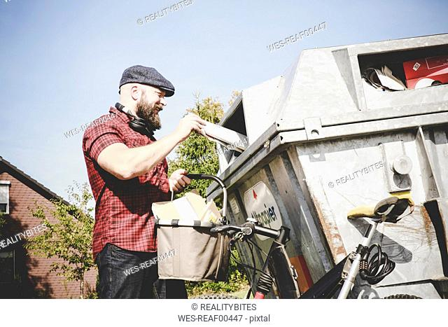 Cyclist recycling waste paper in paper bank