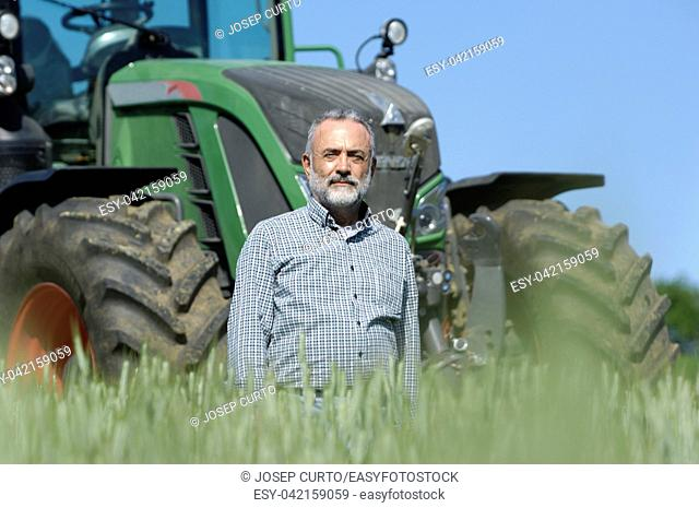 portrait of a farmer with tractor on background