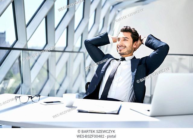 Smiling businessman leaning back at desk in modern office