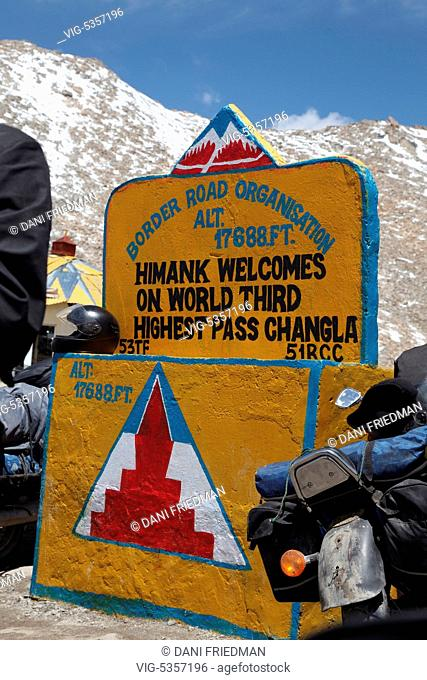 Moterbikes parked by the marker at the top of the Chang La Pass in Ladakh, India. Chang La Pass is located at an elevation of 5,360 meters (17