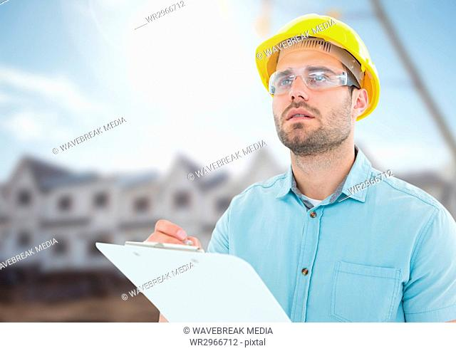 Architect with blueprints on building site