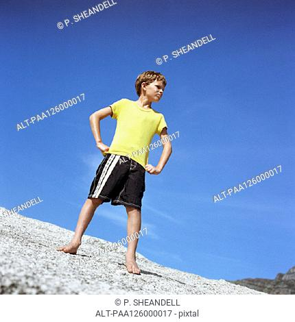 Boy standing with hands on hips, low angle view