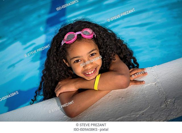 Portrait of girl with curly black hair hanging on edge of swimming pool, looking at camera smiling