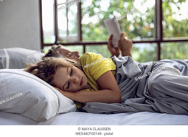 Girl lying in bed with father reading book