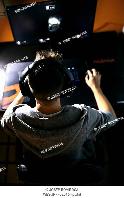 Young man sitting at his PC, playing computer games