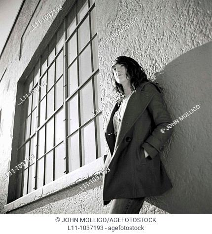 Young woman, leaning on building