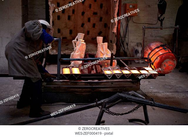 South Africa, Cape Town, Molten bronze being poured into shells for casting