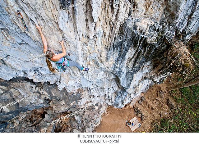 Young female climber climbing a 7a route at Crazy Horse Buttress close to Chiang Mai, Thailand