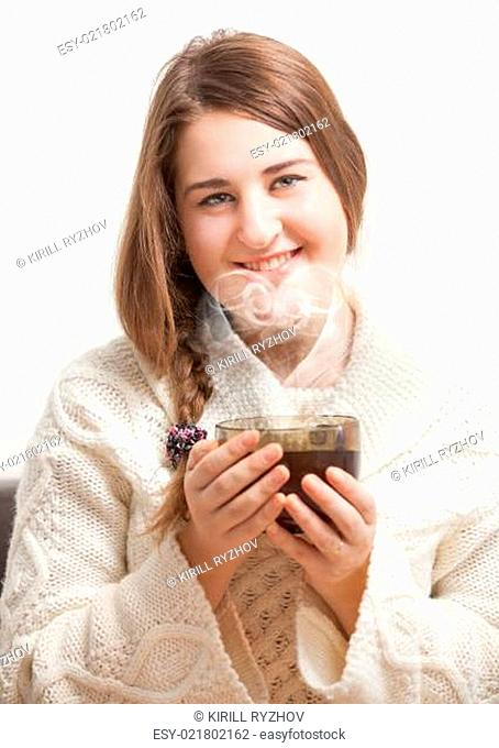 Brunette woman holding cup of tea. Vapor forming heart