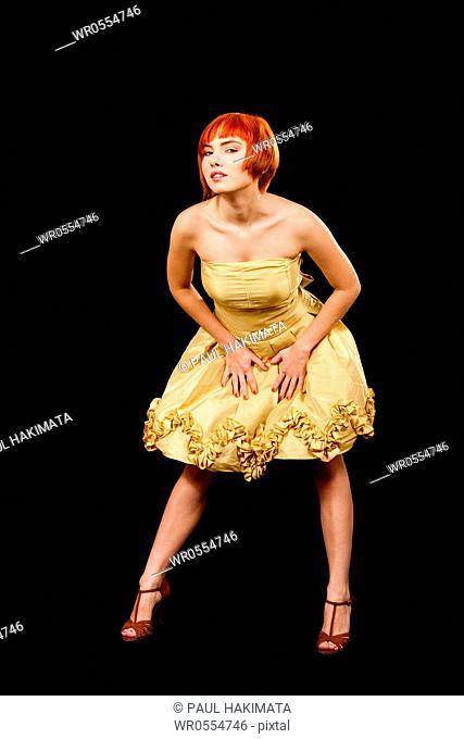 Beautiful Caucasian redhead woman in yellow cocktail dress, isolated