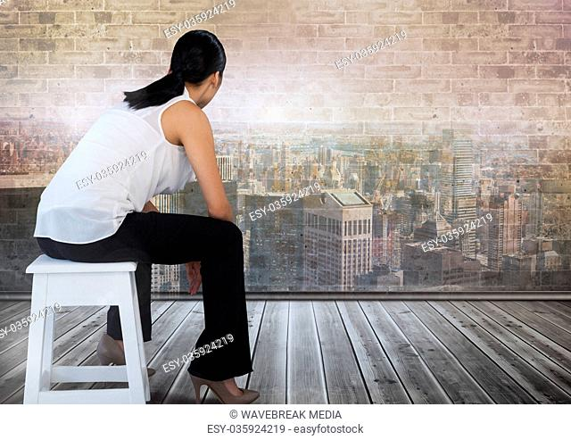 Businesswoman sitting on stool looking out over city