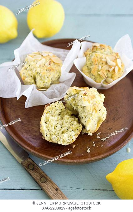 A white plate of wax paper wrapped lemon poppy seed almond muffins, with lemons in the background
