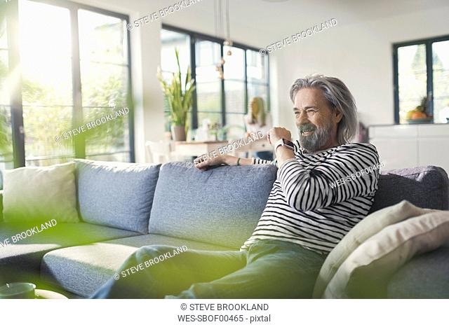 Senior man sitting on couch, talking into smartwatch